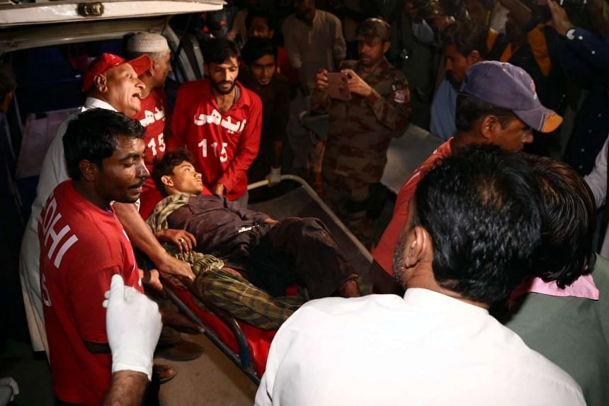 Medics carry a man who was injured in the bomb blast.