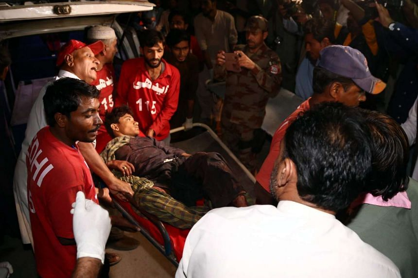 Medics carry a man who was injured in a bomb blast that killed 43 people at a Muslim shrine in southwestern Pakistan.