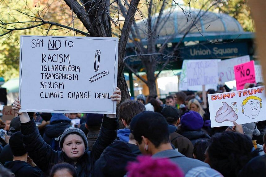 A woman holds a poster regarding safety pins as a sign of solidarity during a protest against US President-elect Donald Trump at Union Square in New York.