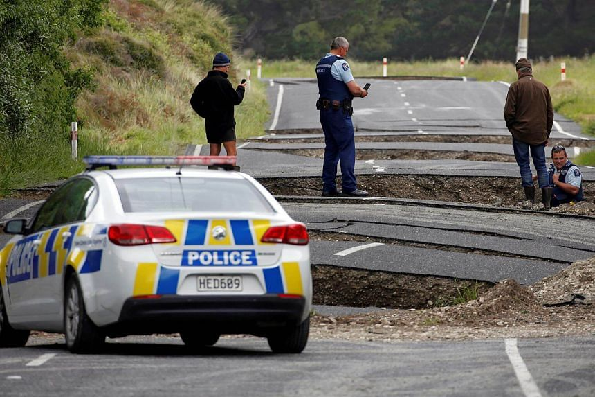 Policemen and locals look at damage following an earthquake, along State Highway One near the town of Ward, south of Blenheim on New Zealand's South Island on Nov 14, 2016.
