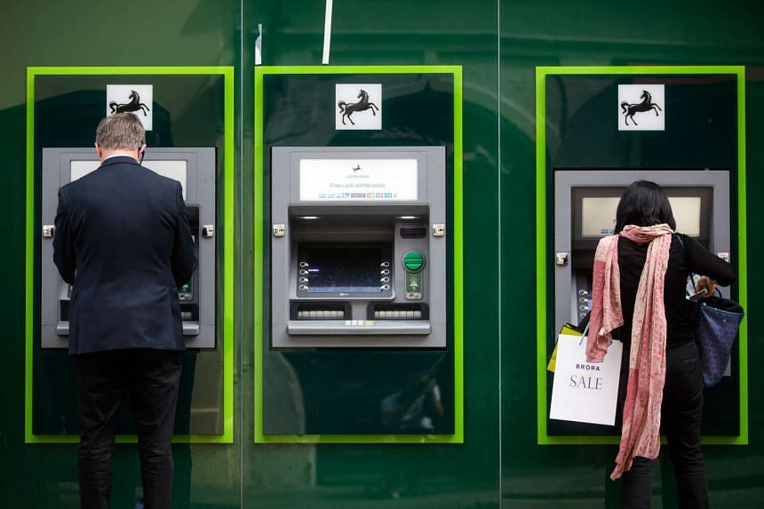 Customers use automated teller machines outside a Lloyds Bank branch, a unit of Lloyds Banking Group Plc, in London, UK, on July 28, 2016.