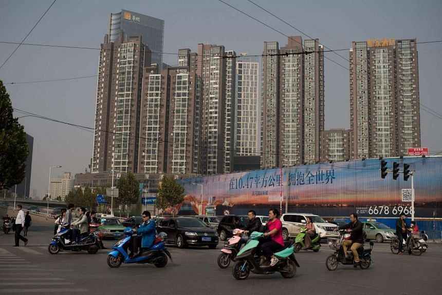 People riding electric bikes as they pass next to property condeminiums (back) in Zhengzhou, on Oct19, 2016.