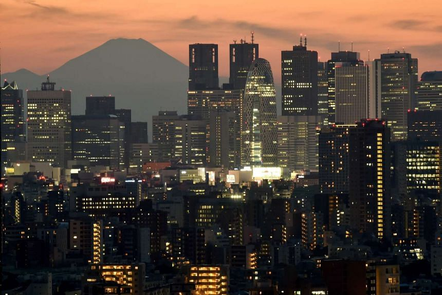 Japan's highest mountain, Mount Fuji at 3,776m, seen behind skyscrapers in Tokyo's Shinjuku area at sunset on Oct 15, 2016.