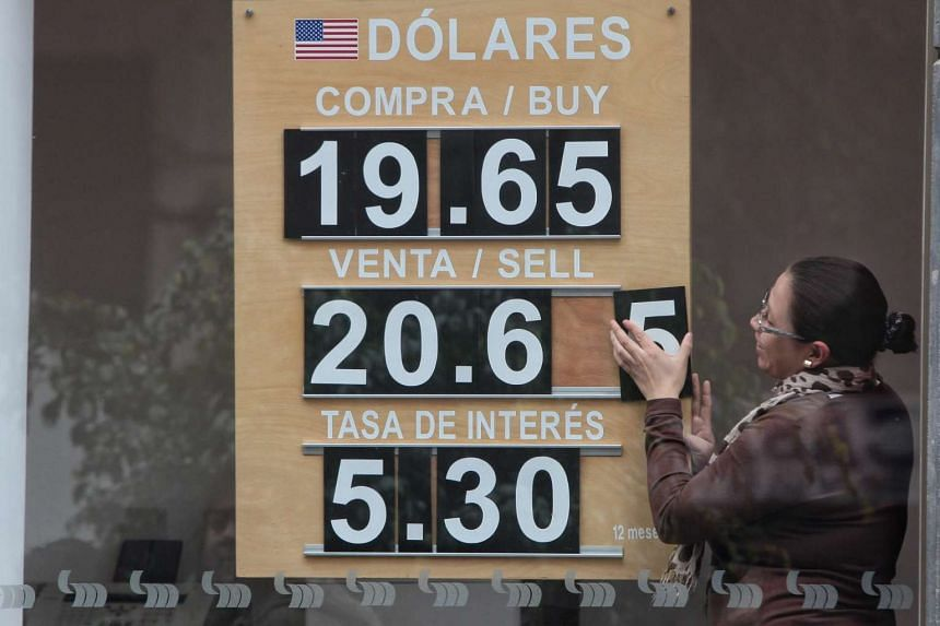A woman changes the numbers in a board showing the price of US dollars in Mexico City, Mexico on Nov 9, 2016.