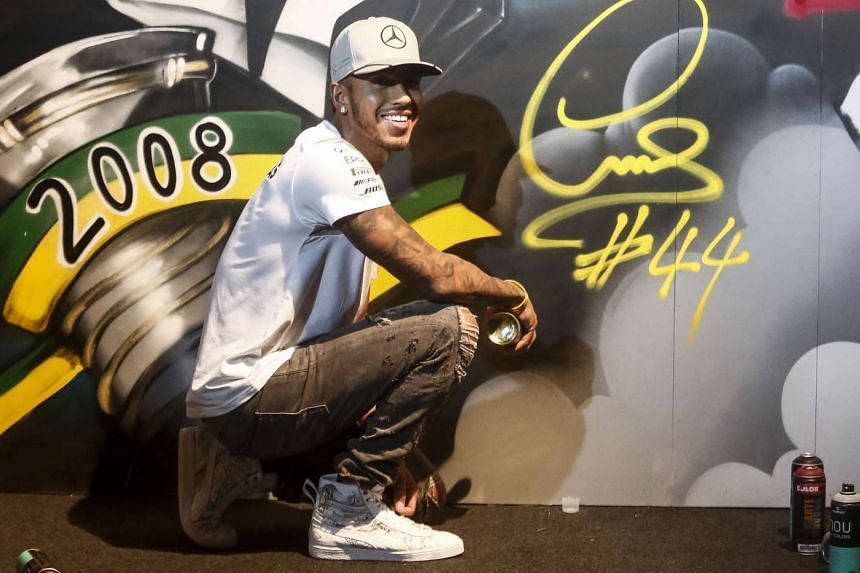 Mercedes AMG Petronas F1 Team British driver Lewis Hamilton poses after signing a graffiti in Sao Paulo, on Nov 9, 2016.
