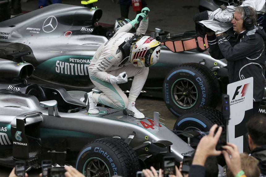 Lewis Hamilton celebrates atop his car after winning the Brazilian GP.