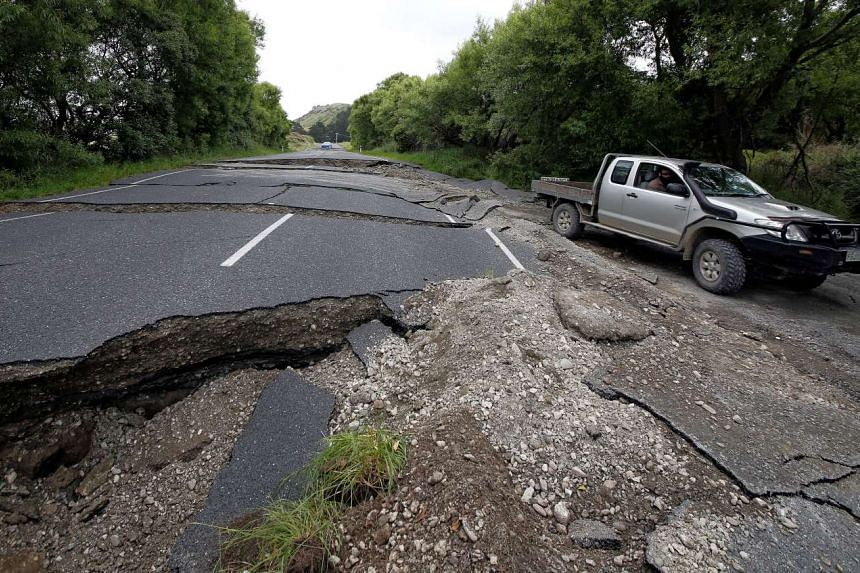 A four-wheel-drive vehicle negotiating the damaged State Highway One near the town of Ward, south of Blenheim, following an earthquake on New Zealand's South Island, on Nov 14, 2016.