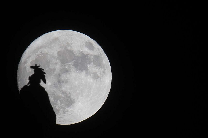 A supermoon rises over the Statue of Freedom on the Capitol dome in Washington, DC on Nov 13, 2016.