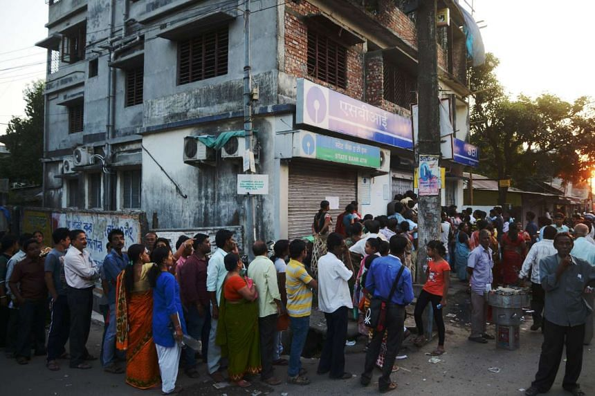 Customers queue outside a bank near a shuttered ATM as they wait to try to exchange 500 and 1000 rupee notes and deposit money in Siliguri, India on Nov 13, 2016.