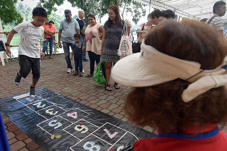 Permanent resident Kevin Lin Thant Zin (left), 10, playing a game of hopscotch at the Singapore Zoo, during an event aiming to foster ties between Singaporeans, permanent residents and foreigners.