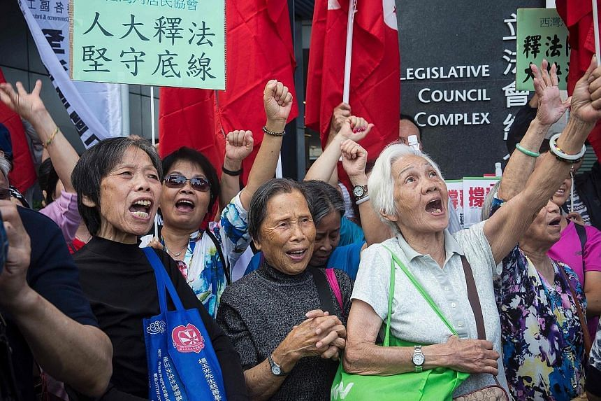 Pro-Beijing demonstrators shouting slogans outside the Hong Kong Legislative Council yesterday, during a rally in support of an interpretation of the city's Constitution.