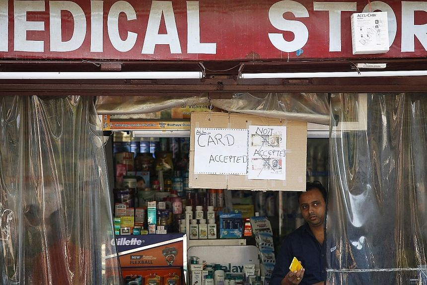 The sign at a medical store in Lucknow stating its refusal to accept the old 500 rupee and 1,000 rupee notes. The move to pull the high-denomination notes from circulation has left millions scrambling to withdraw cash for daily expenses at local shop