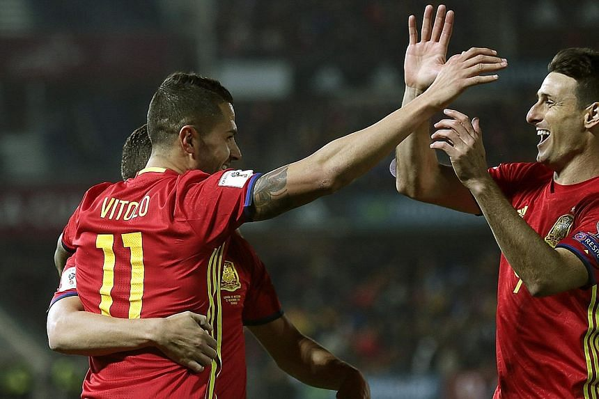 Spaniard Vitolo celebrating his goal with team-mate Aritz Aduriz (right) during the World Cup qualifier against Macedonia. Spain won 4-0 to top Group G on goal difference, ahead of Italy.