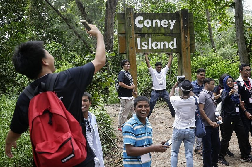 Bangladeshi worker Nasir (who goes by one name), a 41-year-old who works as an assistant supervisor in a shipyard, posing for photographs under the Coney Island signboard during a walk yesterday. The event was organised by some young people from Outw