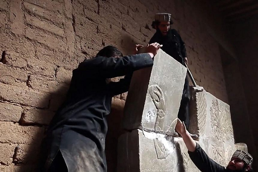 An image from a video showing ISIS militants destroying an artefact in the ancient Assyrian city of Nimrud in northern Iraq last year. The extremists' campaign of destruction against heritage sites also included ancient Nineveh on the outskirts of Mo