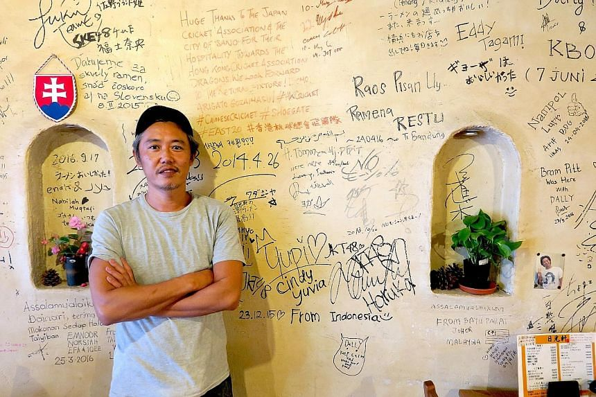 Above: Mr Goka,the owner of Nikkoken restaurant in Sano city, in front of a wall on which customers have left their mark. Every year, the restaurant serves around 1,000 Muslim tourists from places such as Indonesia and Saudi Arabia. Left: Sekai Cafe