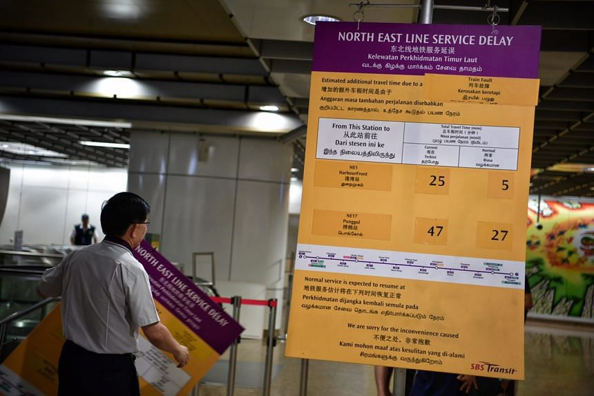 An SBS Transit staff member puts up an information board at Chinatown station to alert commuters to the delay on the NEL.