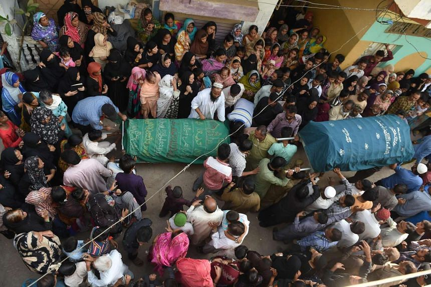 Pakistani mourners surrounding the coffin of a relative killed in a bomb attack on the Shah Noorani Sufi shrine ahead of his funeral in Karachi on Nov 13, 2016.