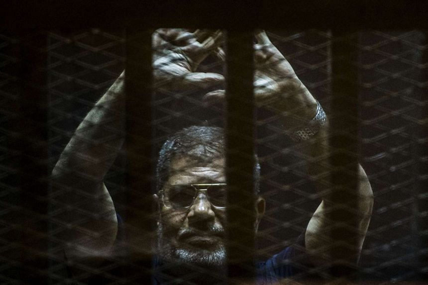 Ousted Egyptian president Mohamed Morsi gesturing from the defendants cage at his trial on June 2, 2015.