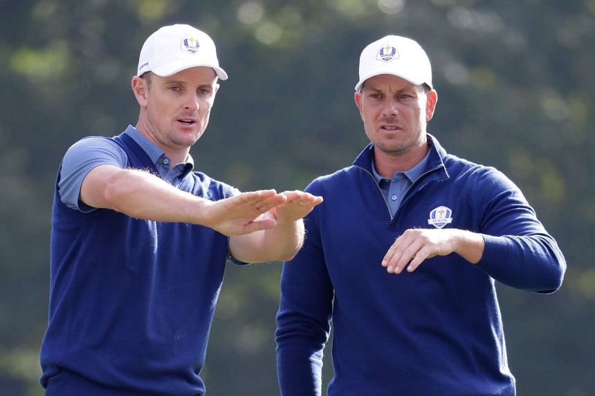 Justin Rose and Henrik Stenson talk on the 13th hole during a match at the Ryder Cup.