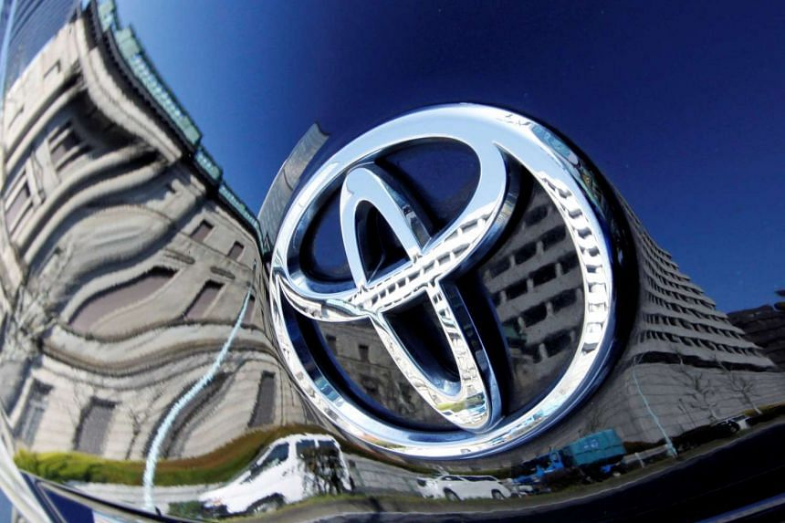 The Bank of Japan building is reflected on Toyota Motor Corp's Prius hybrid car in Tokyo on Feb 18, 2010.