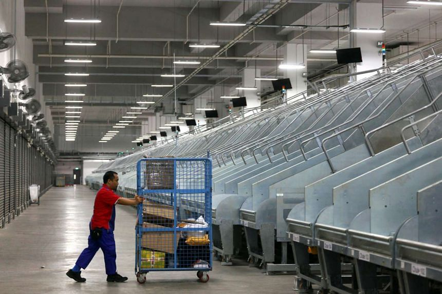 Staff at work at SingPost's regional e-commerce logistics hub at Greenwich Drive.