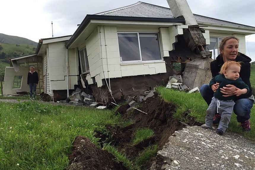 A woman and child in front of a quake-damaged house that sits on the fault line at Bluff Station near Kaikoura on New Zealand's South Island east coast, on Nov 14, 2016.