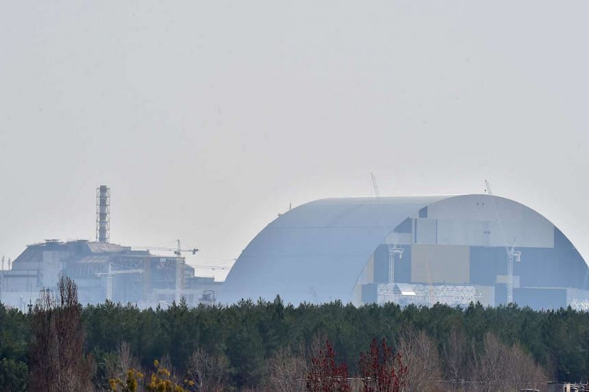 The 4th block of Chernobyl's Nuclear Power Plant (left) and Chernobyl's New Safe Confinement (right) as seen on April 8, 2016.