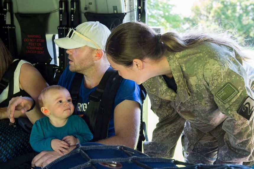 A Royal New Zealand Air Force member (right) helps evacuate a toddler and others aboard an NH90 helicopter from Kaikoura.