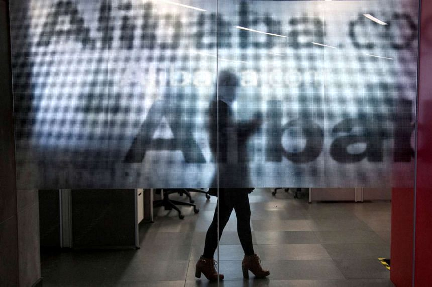 An employee is seen behind a glass wall with the logo of Alibaba at the company's headquarters on the outskirts of Hangzhou, Zhejiang province, April 23, 2014.