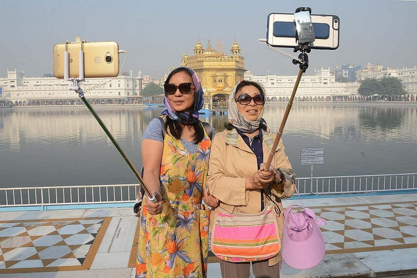 Chinese tourists taking selfies yesterday in front of the Golden Temple in Amritsar, in the north-western Indian state of Punjab, as Sikh devotees marked the 547th birth anniversary of Guru Nanak. Many devotees gathered at the temple and other sites