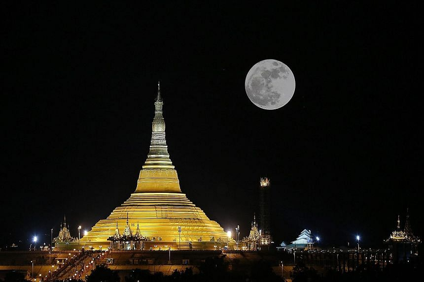 In Singapore (above), enthusiasts gathered at The Pinnacle@Duxton rooftop yesterday but failed to get a glimpse of the supermoon. In Myanmar (left), the supermoon could be seen near the Uppatasanti Pagoda.