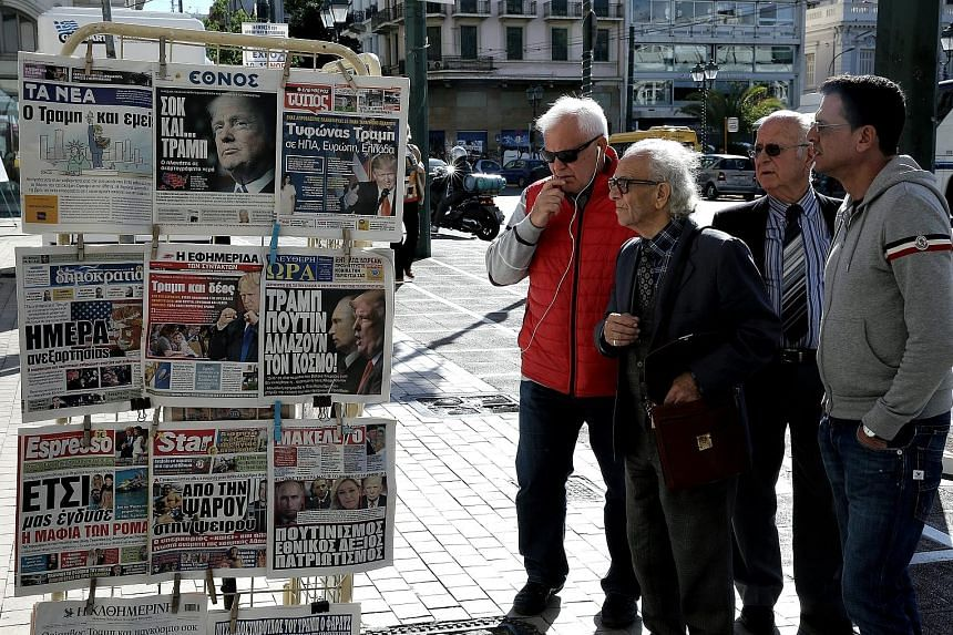 People in the Greek capital Athens reading the front pages of newspapers featuring the election of Mr Donald Trump as the next US president.