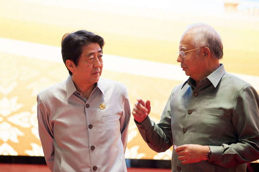 Japanese Prime Minister Shinzo Abe (right) chats with Malaysia's Prime Minister Najib Razak during the gala dinner on the second day of the Association of Southeast Asian Nations (Asean) Summit in Vientiane on Sept 7, 2016.