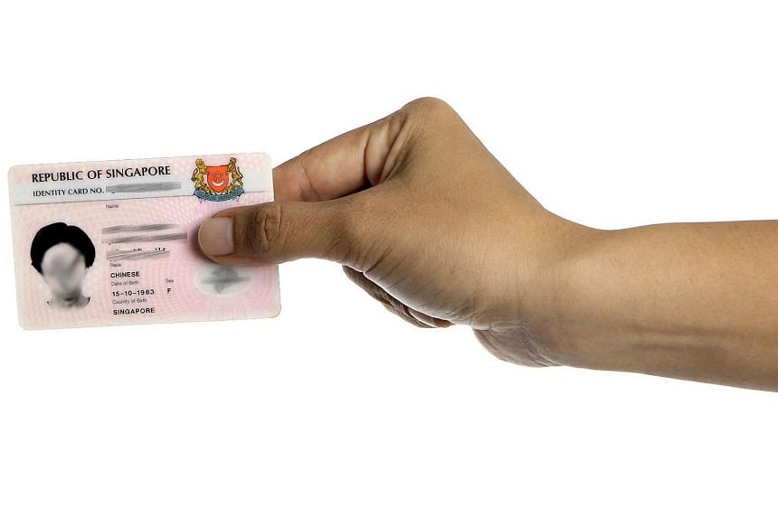 Right hand holding on to a pink Singapore identity card against a white background.