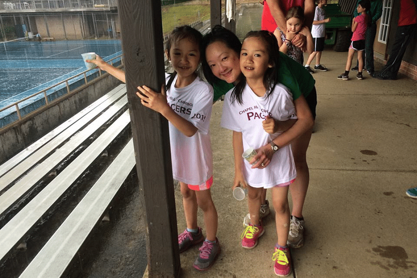 The Straits Times journalist Sharon Loh with the youngest Htoo children, Juno and Janne, both 8, at a cross country practice in March last year.