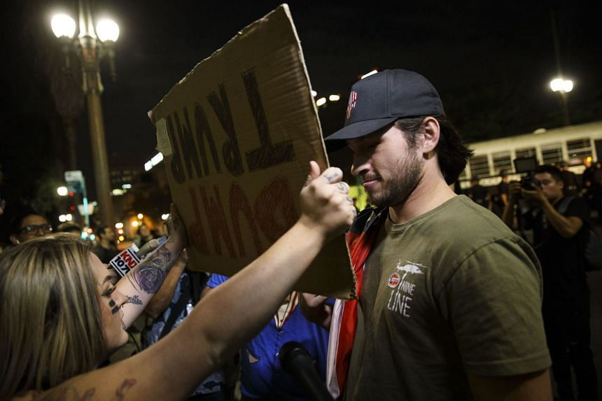 An anti-Trump demonstrator holds a sign in front of a Trump supporter during a protest near City Hall in Los Angeles last Saturday. America has to put its house in order first.