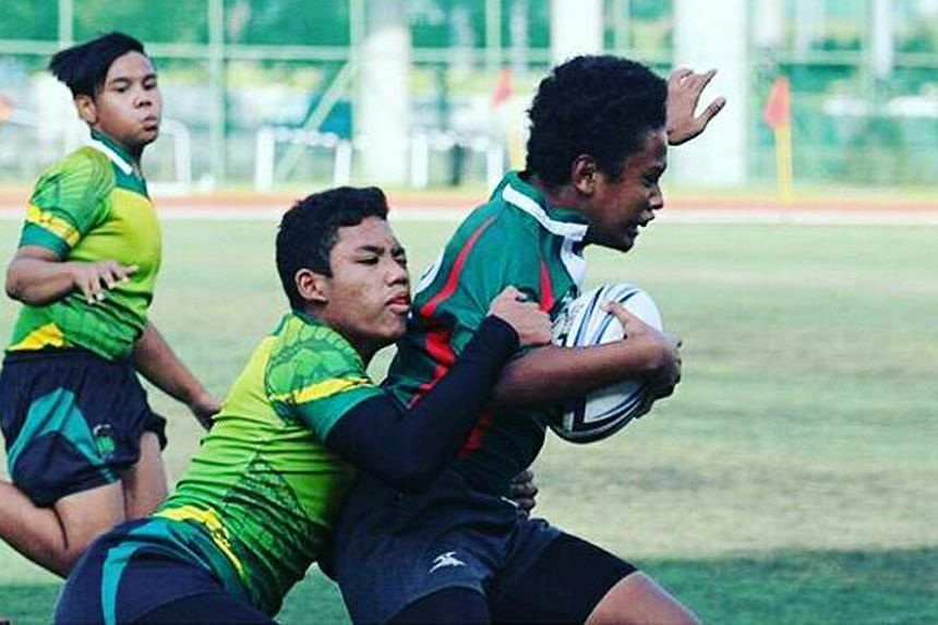 Azyzul Azhar of Pioneer Secondary tackling Greenridge Secondary player Fa'dly Hasry in an Under-14 game at the Saints 7s tournament. Azyzul knows competition is stiff in St Andrew's but he is making the switch to improve his skills and help him r