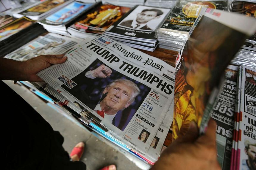 A person looks at a newspaper displaying Donald Trump's US election victory at a book shop in Bangkok, Thailand.