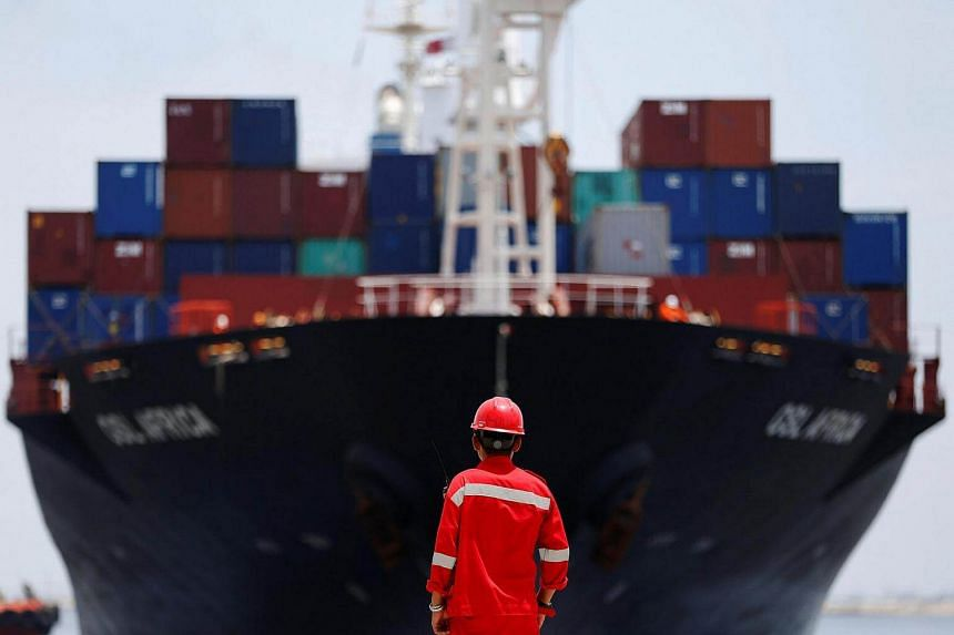 A port worker watches as a ship leaves the New Priok Container Terminal 1 in North Jakarta.