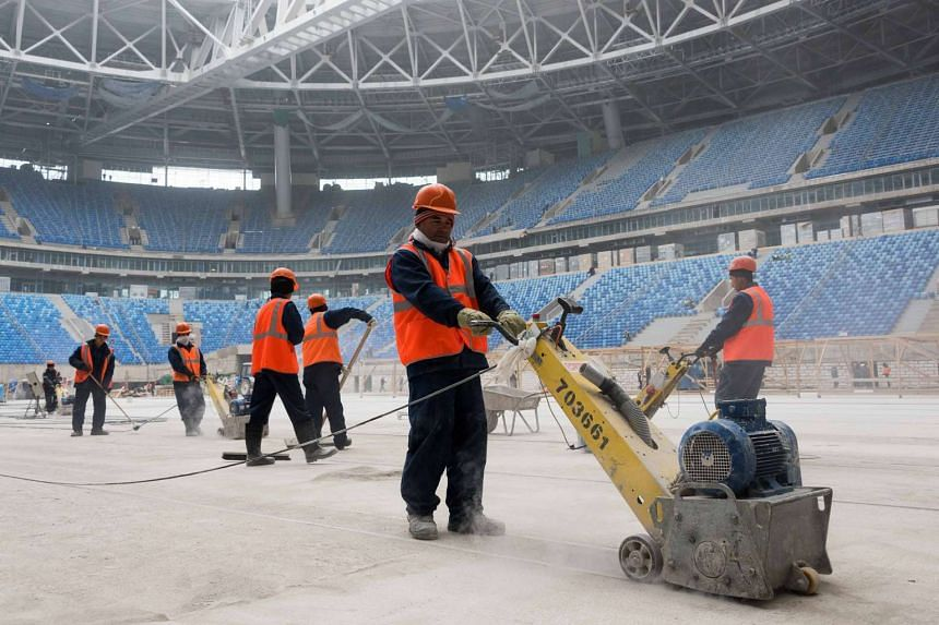 Workers at the Saint-Petersburg Stadium on Oct 3, 2016, during construction works ahead of the World Cup 2018 football tournament.