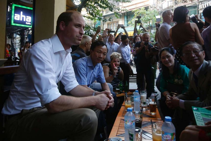 Britain's Prince William (left) chats with Vietnamese residents at a cafe at the old quarters of Hanoi on Nov 16, 2016.