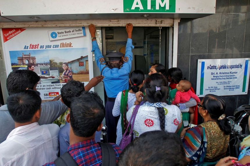 A security guard closes the shutter of State Bank of India ATM after it stopped dispensing cash in Agartala, India on Nov 15, 2016.
