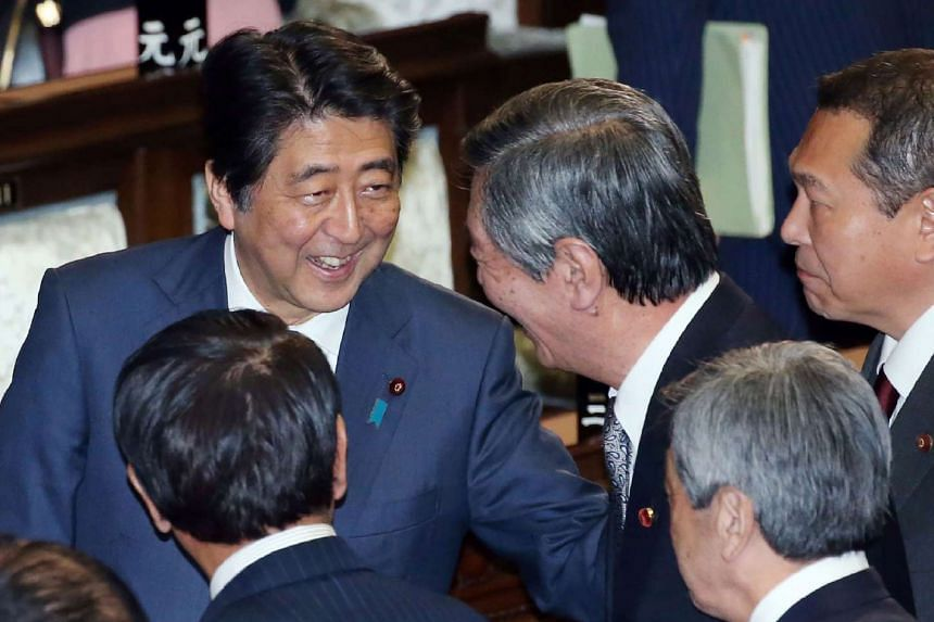 Japan's Prime Minister Shinzo Abe (left) smiles with other lawmakers after the Trans-Pacific Partnership (TPP) free trade deal was passed in the lower house of the parliament in Tokyo on Nov 10, 2016.