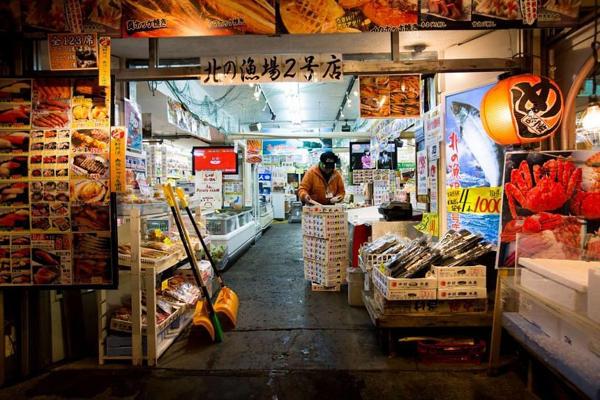 A vendor arranges seafood at a store in the Sapporo Curb Market at dawn in Sapporo, Hokkaido, Japan, on Nov 15, 2016.