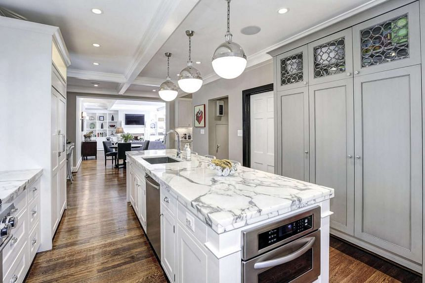 The kitchen features marble countertops and white cabinets as well as a hardwood floor.