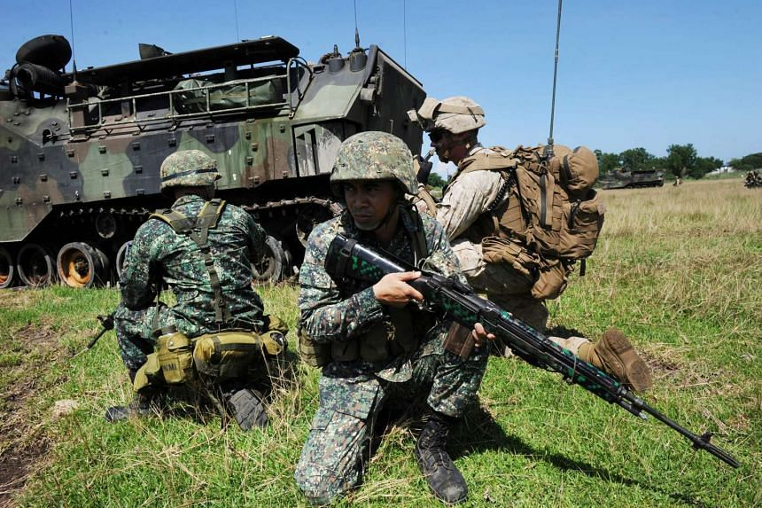 Philippine (in green) and US (in light brown) marines during the annual Philippines-US amphibious landing exercise at the navy base facing the South China Sea in San Antonio, Zambales province on Oct 9, 2015.