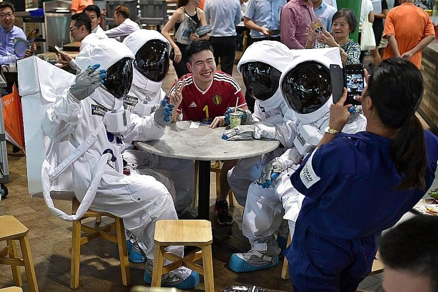 "A man having his picture taken with a group of ""astronauts"" during lunch hour at Lau Pa Sat on Monday. The four ""astronauts"" went around the food centre entertaining people with their antics as part of the ArtScience Museum's promotion of its new exh"
