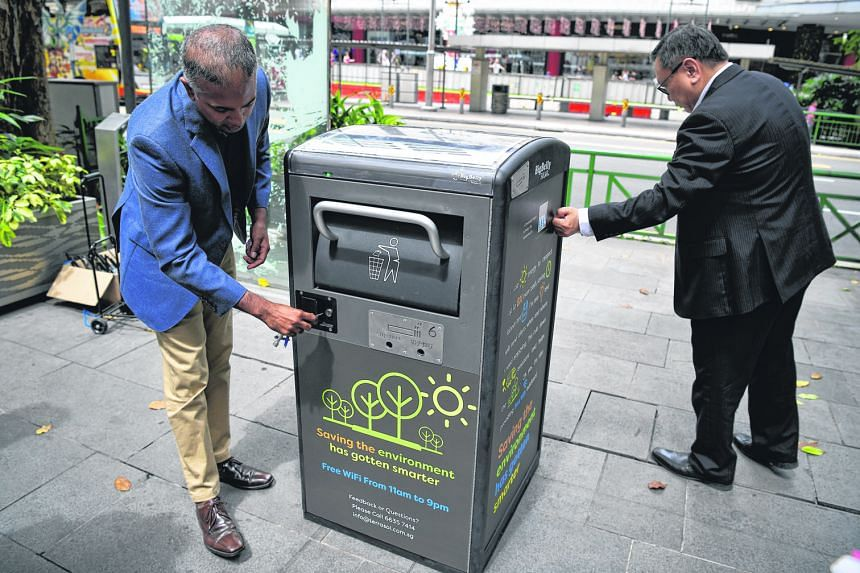 """Mr Jason Kumar (left), co-founder of technology firm Terra Sol, and Orchard Road Business Association (Orba) executive director Steven Goh showing the uses of one of the solar-powered Bigbelly """"smart"""" bins in Orchard Road yesterday. Each bin can crun"""