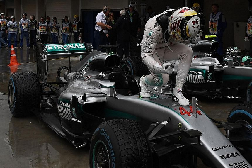 Mercedes' Lewis Hamilton celebrating his Brazilian Grand Prix win to take the race for the driver's championship down to the wire. He trails his team-mate Nico Rosberg by 12 points ahead of the Abu Dhabi race.
